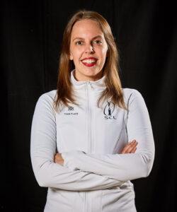 Kuvassa hymyilevä päävalmentaja Maria Wahlroos. Marialla on yllään SCL:n valkoinen fleece ja hänen kätensä on puuskassa.