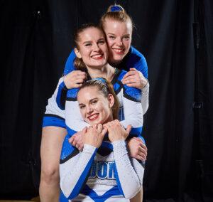 Kuvassa kolme maajoukkueen naisurheilijaa jonomaisesti. Keskimmäinen halaa ensimmäistä ja viimeisen urheilijan kädet on keskimmäisen urheilijan harteilla. Urheilijat hymyilevät-
