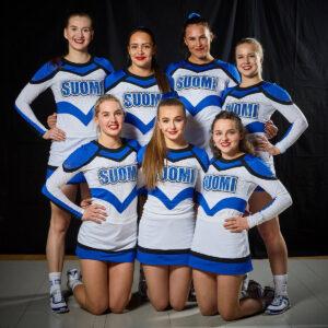 Kuvassa seitsemän naisten cheermaajoukkueen urheilijaa. Neljä takarivin urheilijaa seisoo, kolme eturivin urheilijaa on polviseisonnassa. Reunimmaisimmilla urheilijoilla on käsi lanteilla. Urheilijoilla on päällään sinivalkoinen kisa-asu. Kaikki hymyilevät.