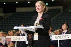 Kuvassa Taru Rautavuori-Knabe pitämässä käsissään viikattua Suomen lippua. Taru hymyilee mustassa jakkupuvussa. Takana näkyy cheerleadingjoukkueita palkinnonjaossa.