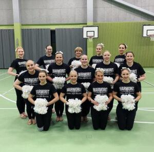 Kuvassa neljätoista joukkuelaista asetelmassa. Päällään heillä on mustat esiintymisasut ja käsissä valkoiset huiskat.